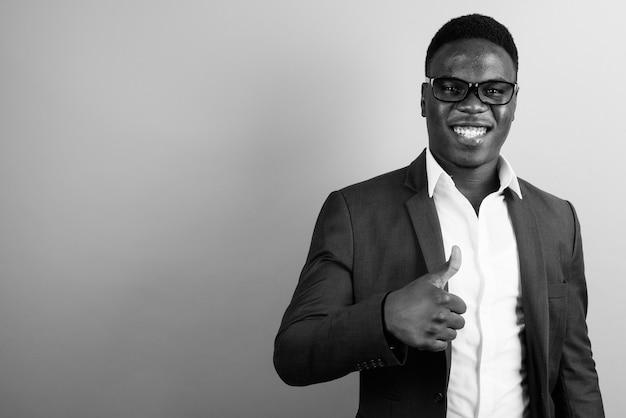 Jovem empresário africano vestindo terno contra uma parede branca. preto e branco