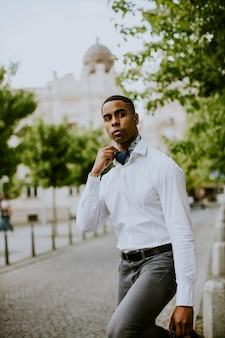 Jovem empresário afro-americano à espera de um táxi numa rua