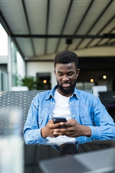 Jovem empresário afro-americano com óculos e laptop sentado no café bar e usar o telefone celular.