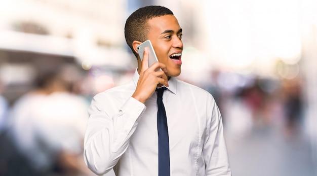 Jovem empresário afro-americano, mantendo uma conversa com o celular na cidade