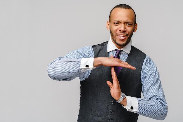 Jovem empresário afro-americano mostrando um gesto de pausa de tempo limite com as mãos