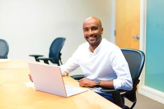 Jovem empresário afro americano no escritório com seu laptop