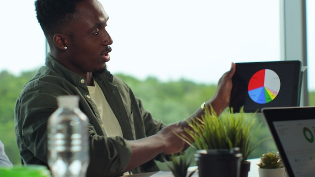 Jovem empresário afro-americano olhando para a tela do tabletpc e discutindo um novo projeto de inicialização em uma reunião de negócios de escritório moderno no escritório de uma empresa iniciante