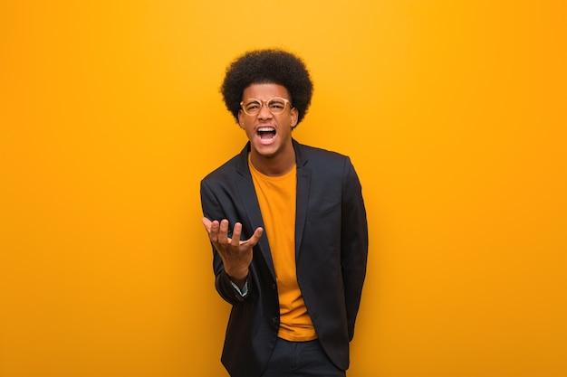 Jovem empresário afro-americano sobre uma parede laranja muito assustado e com medo