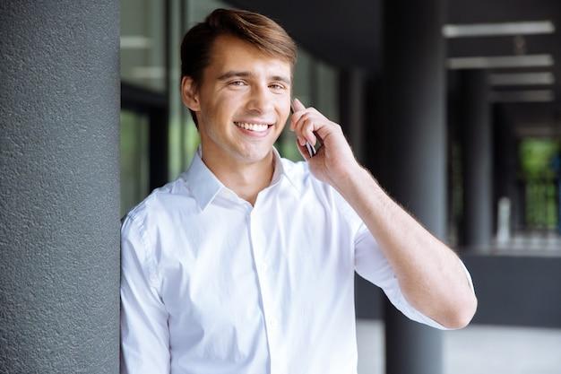 Jovem empresário alegre falando no celular perto do centro de negócios