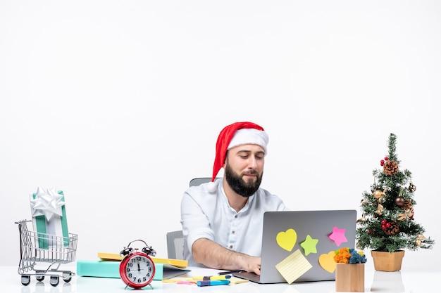 Jovem empresário alegre no escritório comemorando o ano novo ou o natal trabalhando sozinho no fundo branco
