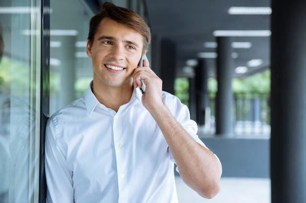Jovem empresário alegre segurando um laptop e falando no celular, perto do centro de negócios