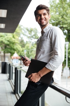 Jovem empresário alegre segurando uma pasta e usando o celular ao ar livre