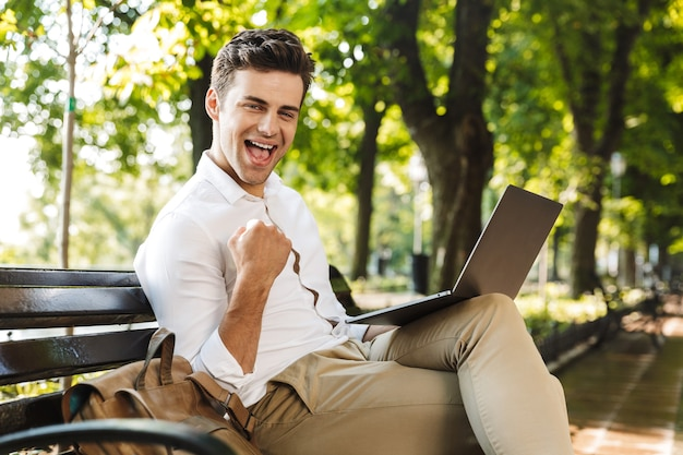 Jovem empresário alegre sentado em um banco ao ar livre, trabalhando em um laptop, comemorando o sucesso