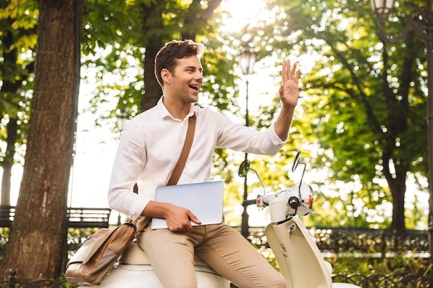 Jovem empresário alegre sentado em uma moto ao ar livre, segurando um laptop