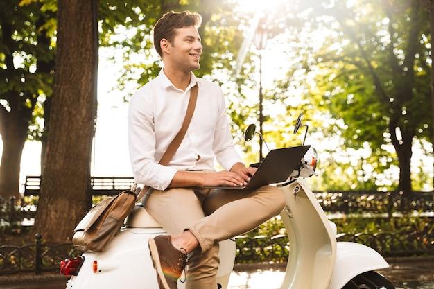Jovem empresário alegre sentado em uma moto ao ar livre, trabalhando em um laptop