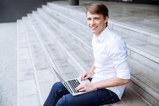 Jovem empresário alegre usando laptop perto do centro de negócios