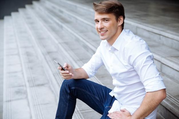Jovem empresário alegre usando smartphone perto do centro de negócios