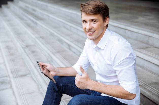 Jovem empresário alegre usando tablet perto do centro de negócios