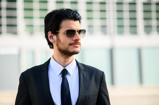 Jovem empresário ao ar livre usando óculos escuros