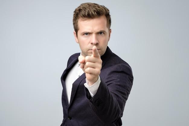 Jovem empresário apontando com o dedo para a câmera e para você