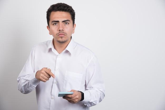 Jovem empresário apontando para blocos de notas em fundo branco.
