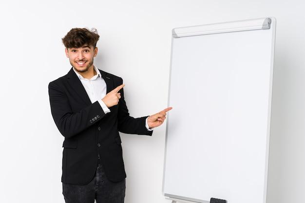 Jovem empresário árabe como treinador chocado, apontando com o dedo indicador para um espaço de cópia.