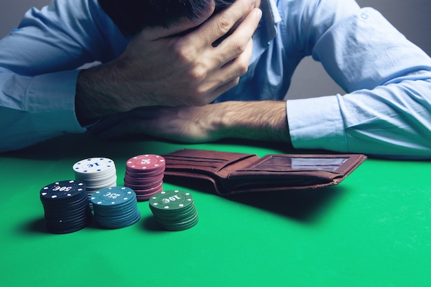 Jovem empresário arrasado perdendo pôquer no cassino