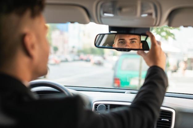 Jovem empresário arrumando seu espelho retrovisor