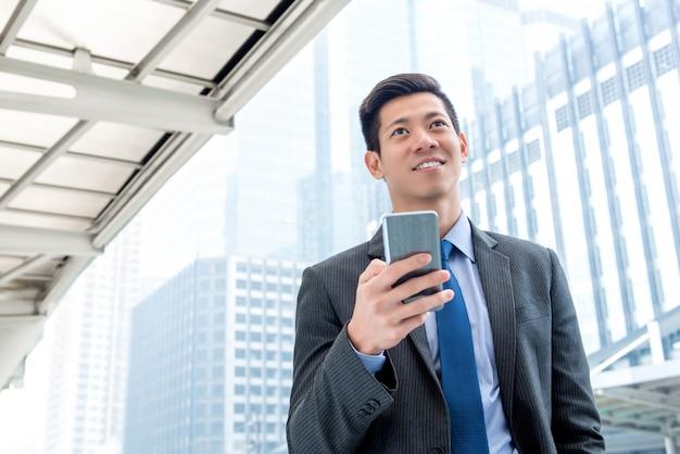 Jovem empresário asiático bonito usando telefone celular ao ar livre