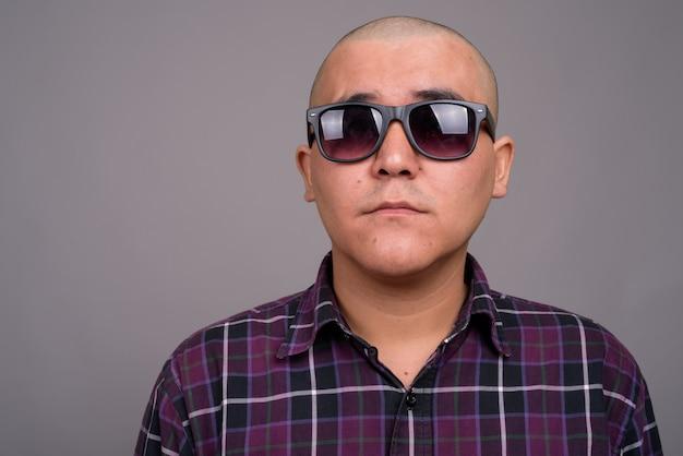 Jovem empresário asiático careca vestindo camisa quadriculada contra parede cinza