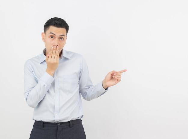 Jovem empresário asiático com camisa azul animado com as mãos cobrindo a boca