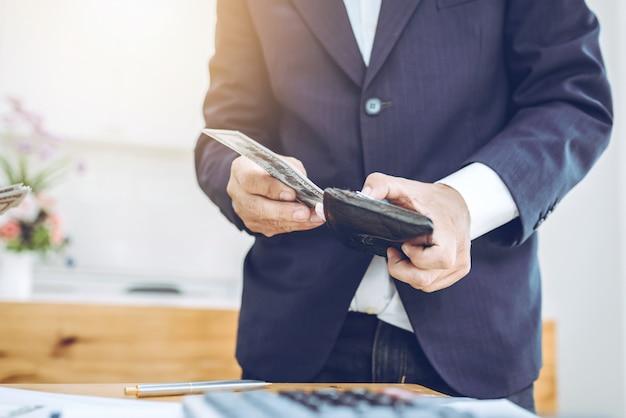 Jovem empresário asiático com conta e carteira de dinheiro.