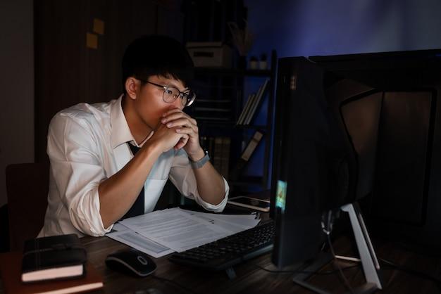 Jovem empresário asiático concentrado trabalhando até tarde