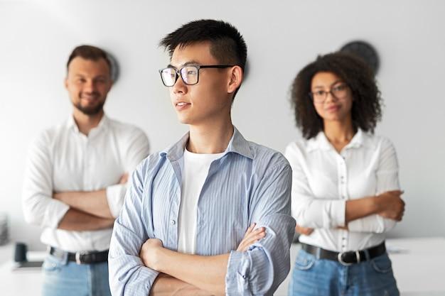 Jovem empresário asiático de sucesso confiante em óculos e roupa casual olhando para longe enquanto está em um escritório leve com colegas de trabalho positivos no fundo