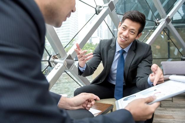Jovem empresário asiático discutindo gráficos estatísticos financeiros com seu parceiro