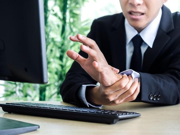 Jovem empresário asiático em terno sentindo dor nas mãos ao usar um notebook no escritório