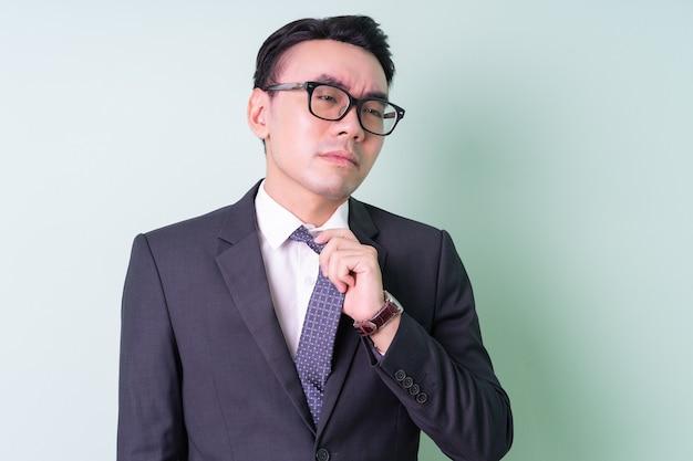 Jovem empresário asiático posando sobre fundo verde