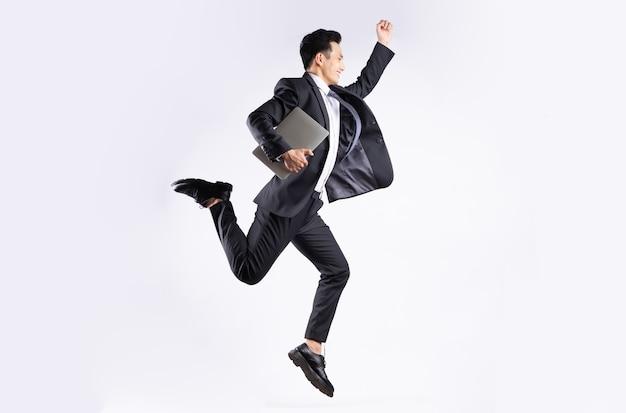 Jovem empresário asiático pulando no branco
