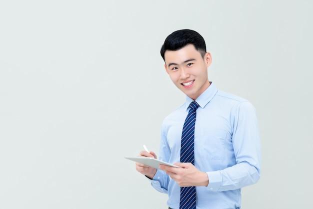 Jovem empresário asiático sorridente usando tablet digital com caneta stylus eu