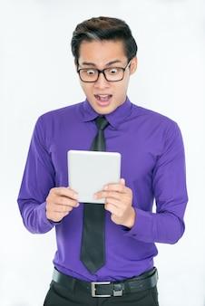Jovem empresário asiático surpreendido lendo notícias