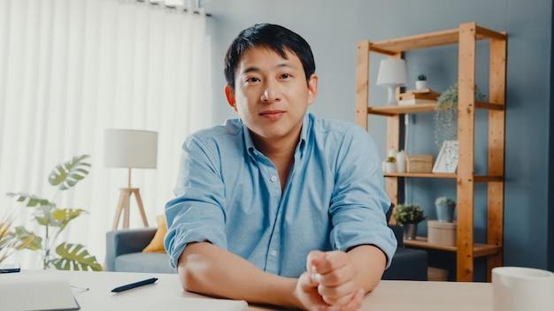 Jovem empresário asiático usando computador laptop fala com colegas sobre o plano de uma reunião de videochamada enquanto trabalha em casa