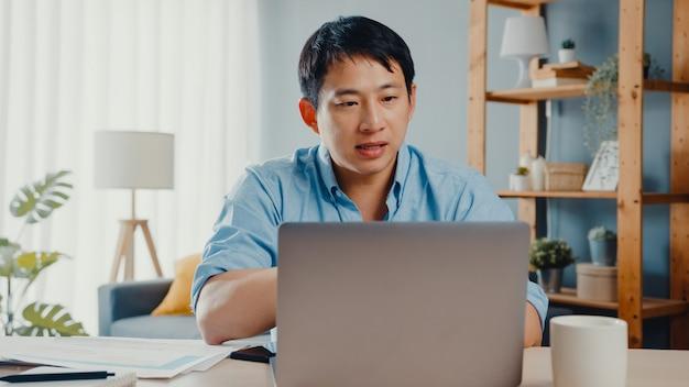Jovem empresário asiático usando laptop fala com colegas sobre o plano em videochamada enquanto trabalha em casa.