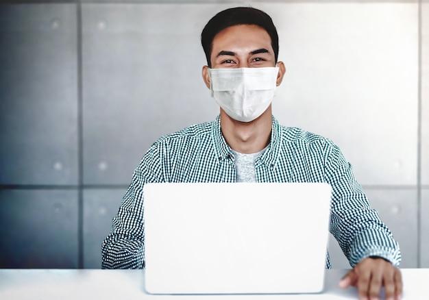 Jovem empresário asiático usando máscara cirúrgica no escritório. sentado na mesa enquanto trabalhava no computador portátil.