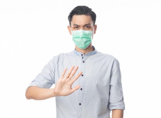 Jovem empresário asiático usando máscara higiênica, gesticulando parada para evitar infecção, 2019-ncov ou coronavírus.