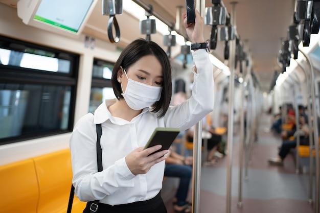 Jovem empresário asiático usando máscara usa um telefone no metrô. conceito de infecção e surto.