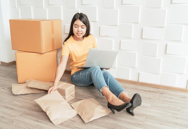 Jovem empresário asiático usando o computador para verificar os pedidos dos clientes e preparar pacotes
