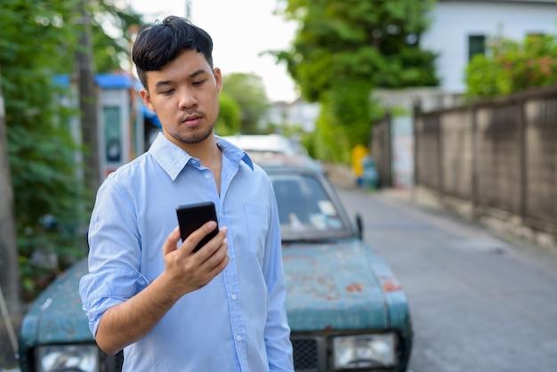 Jovem empresário asiático usando telefone celular contra um carro velho e enferrujado