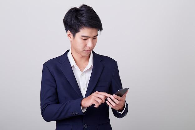 Jovem empresário asiático usando um telefone inteligente