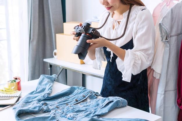 Jovem empresário asiático, usando uma câmera, tira uma foto de um produto para carregá-lo na loja online do site.