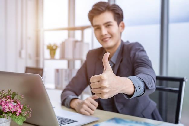 Jovem empresário asiático vê um plano de negócios de sucesso no laptop e no papel de documento. foco borrão abstrato mostrando os polegares para cima no fundo da mesa de madeira no escritório