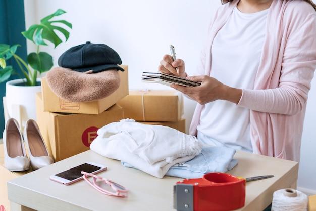 Jovem empresário asiático, verificando o saldo de estoque e escrevendo no caderno com itens de moda na mesa.