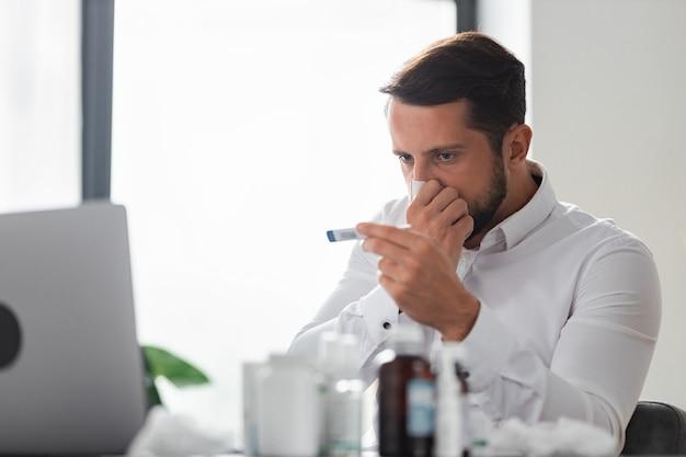 Jovem empresário assoa o nariz e mede a temperatura com um termômetro enquanto está sentado no escritório, vírus da gripe, resfriado, mal-estar conceito