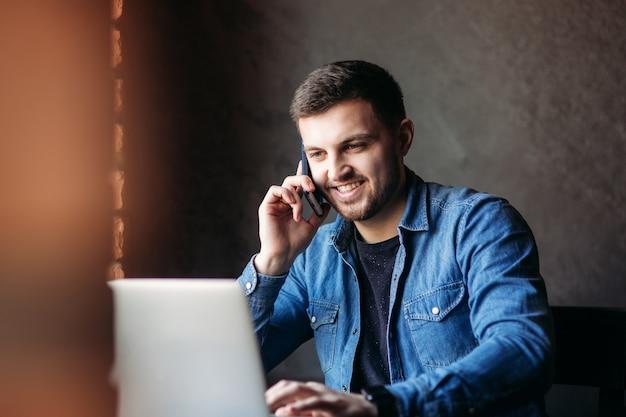 Jovem empresário atendendo uma ligação em um café enquanto usa um laptop