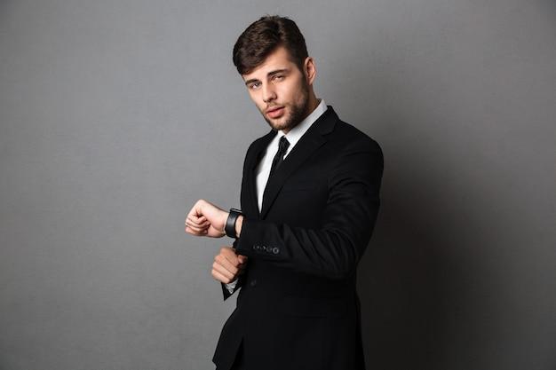 Jovem empresário atraente com roupa formal, verificando o tempo em seu relógio de pulso,
